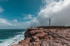 Cape Nelson lighthouse standing on a rugged cliff above ocean under stormy skies. Victoria, Australia. Stock Photography