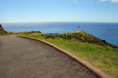 Cape Reinga Lighthouse in the distance. Lighthouse located in the north edge of New Zealand, Cape Reinga is seen in the distance with path leading to it stock image