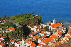 Cape rock and town on coast. Camara-de-Lobos, Madeira, Portugal Stock Images