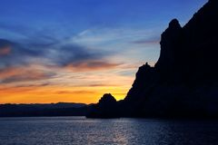 Cape San Antonio Javea Xabia sunset from sea. Cape San Antonio Javea Xabia sunset view from sea Mediterranean backlight Alicante Spain Stock Images