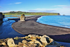 Cape in southern Iceland. On an ocean beach with volcanic sand is a huge rock. Cape Dirholaey in southern Iceland royalty free stock photo
