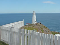 Cape Spear Lighthouse, Newfoundland, CA. White picket fence borders tall, white Cape Spear lighthouse tower which sits on rocky cliff overlooking Atlantic Ocean Royalty Free Stock Photo