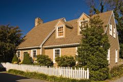 Cape Style House with an Addition. Quaint cape style house with a picket fence in front against a bright blue sky Stock Photo