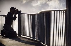 Photographer in silhouette taking photographs Stock Photos