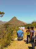 Cape Town - 2011: Schulkinder, einen Maler beobachtend stockfoto