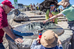CAPE TOWN, SOUTH AFRICA, 18 December 2016: Tourists and visitors. Admiring the bronze outline 3D moulding of Table Mountain on top of Table Mountain, Cape Town Royalty Free Stock Photos