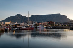 Cape Town V&A Waterfront. Victoria and Alfred Waterfront as the hot summers sun sets behind Table Mountain and the night lights light up everywhere Stock Images