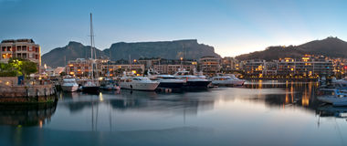 Cape Town V&A Waterfront. Victoria and Alfred Waterfront as the hot summers sun sets behind Table Mountain and the night lights start to shine Royalty Free Stock Photos