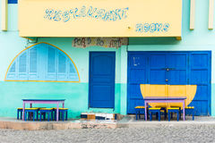 Cape Verde restaurant. Artistic frontage of a village restaurant in Cape Verde. display of green, blue and yellow colors Stock Image