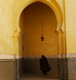Caped figure seen through archway in Meknes, Morocco. A mysterious caped figure is seen leaving the Mausoleum of Moulay Ismail in Meknes, Morocco through a Royalty Free Stock Photography