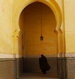 Capedcijfer door overwelfde galerij in Meknes, Marokko wordt gezien dat royalty-vrije stock fotografie