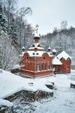 A capela é do tijolo vermelho em um fundo da paisagem do inverno Foto de Stock Royalty Free