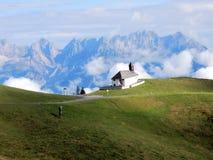 """Capela do †dos cumes dos hel do ¼ de Kitzbà """", montanhas, pastagem, nuvens, cumes orientais centrais pela cidade de Kitzbuhel - Fotos de Stock Royalty Free"""
