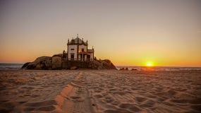 Capela gör Senhor da som Pedra i Miramar nära Porto är en turistic fläck som byggs på stranden med enorm portugisisk havssolnedgå royaltyfri bild