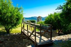 Capela velha da torre de pulso de disparo, ponte de madeira na barra de Stari, Montenegro fotografia de stock royalty free