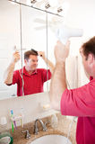 Capelli asciug col foenare dell'uomo in stanza da bagno Immagini Stock