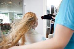 Capelli asciuganti col phon fotografie stock