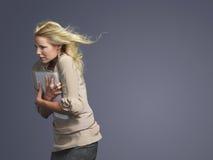 Capelli biondi di With Folder And della donna di affari che soffiano in vento immagini stock libere da diritti