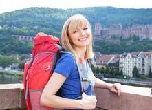 Capelli biondi di risata di viaggiatore con zaino e sacco a pelo a Heidelberg Immagini Stock