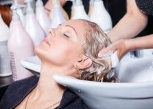 Capelli che lavano ad un salone di lavoro di parrucchiere Fotografie Stock