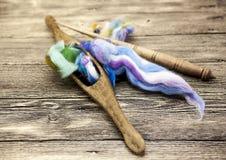Capelli colorati e vecchio primo piano del fuso su fondo di legno Strumenti per tricottare della lana Immagini Stock Libere da Diritti