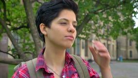 Capelli commoventi del giovane studente di college sicuro ed esaminare macchina fotografica, stante nel parco vicino all'universi video d archivio