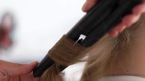 Capelli d'arricciatura del parrucchiere con le tenaglie dei capelli mentre creando acconciatura alla moda nello studio di bellezz stock footage