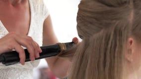 Capelli d'arricciatura del parrucchiere facendo uso delle tenaglie dei capelli vicino su Elabori l'arricciatura longhair con il f video d archivio