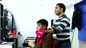 Capelli dei clienti del lavaggio del barbiere stock footage
