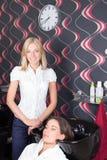 Capelli dei clienti di lavaggio del parrucchiere ad un salone di bellezza Fotografia Stock
