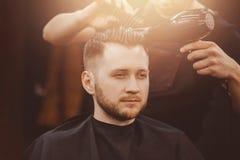 Capelli del cliente di lavaggio del parrucchiere nel negozio di barbiere fotografia stock