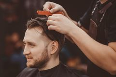 Capelli del cliente di lavaggio del parrucchiere nel negozio di barbiere immagini stock