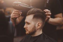 Capelli del cliente di lavaggio del parrucchiere nel negozio di barbiere fotografie stock libere da diritti