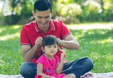 Capelli del papà che vestono la sua neonata Fotografia Stock