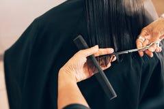 Capelli del ` s del cliente di taglio del parrucchiere nel salone di bellezza fotografie stock