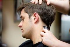 Capelli del suo cliente del parrucchiere taglio Fotografie Stock