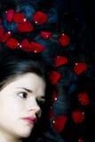 Capelli della donna con i petali di rosa Immagini Stock