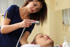 Capelli di lavaggio della donna all'uomo sorridente bello Fotografie Stock