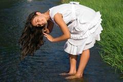 Capelli di lavaggio della ragazza graziosa nel flusso Immagini Stock