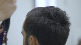 Capelli di secchezza del parrucchiere professionista nel salone di bellezza Giovane cliente maschio e barbiere femminile archivi video