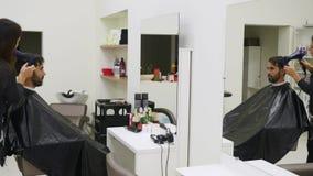 Capelli di secchezza del parrucchiere professionista nel salone di bellezza Giovane cliente maschio e barbiere femminile video d archivio