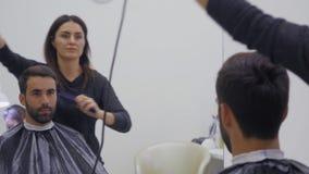 Capelli di secchezza del parrucchiere professionista nel salone di bellezza Giovane cliente maschio e barbiere femminile Fine in  archivi video