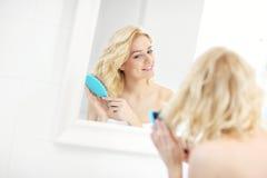 Capelli di spazzolatura della donna Fotografie Stock