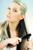 Capelli di spazzolatura della donna Immagini Stock