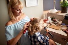 Capelli di spazzolatura della mamma a sua figlia fotografia stock