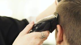 Capelli di taglio con il rasoio elettrico nella fine del parrucchiere su Parrucchiere della donna che lavora con il cliente e che video d archivio