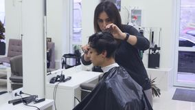 Capelli di taglio della giovane donna al parrucchiere Il parrucchiere taglia i capelli ad una ragazza con forbici professionali archivi video