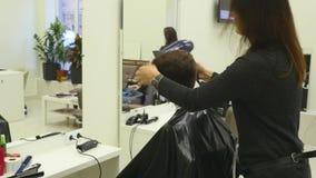 Capelli di taglio della giovane donna al parrucchiere Il parrucchiere taglia i capelli ad una ragazza con forbici professionali video d archivio