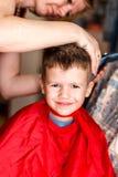Capelli di taglio della madre per il figlio Fotografie Stock Libere da Diritti