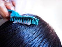Capelli di tintura del parrucchiere professionista del suo cliente immagini stock